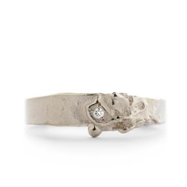 Ring in gold with rough structure and diamond